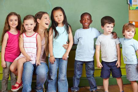 彼女は幼稚園の子供たちのグループとの幸せな保育 写真素材