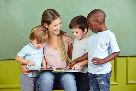 preschool children: Happy child day care worker with children reading a book in kindergarten Stock Photo