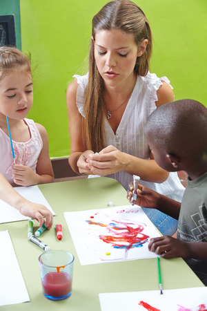 tempera: Children painting with tempera color in kindergarten and a nursery teacher is helping Stock Photo