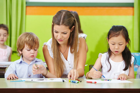 educators: Niños y pintura educadora en el jardín de infantes con pinceles sobre papel