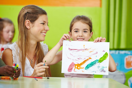 Girl showing self drawn painting in kindergarten with nursery teacher Stock Photo
