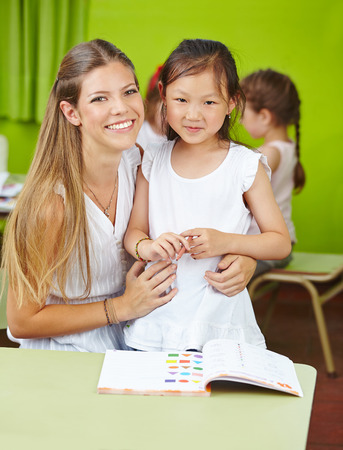playschool: Chinese girl with child care worker in kindergarten learning with a book Stock Photo