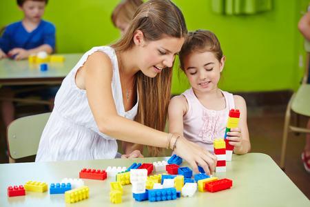 Profesor del cuarto de niños y niñas jugando con los ladrillos del edificio en un jardín de infantes