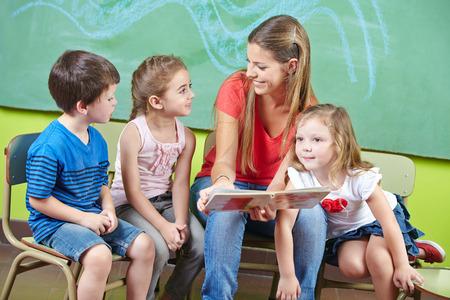 maestra preescolar: Trabajador de cuidado infantil y niños que leen un libro de imágenes juntas en un jardín de infantes Foto de archivo