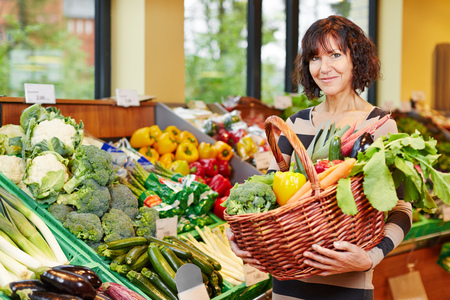 Elderly smiling woman buying fresh vegetables in a supermarket photo