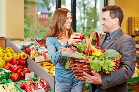 Happy couple in supermarket buying fresh vegetables together photo