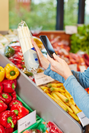 Customer in supermarket scanning barcode of a package asparagus with his smartphone photo