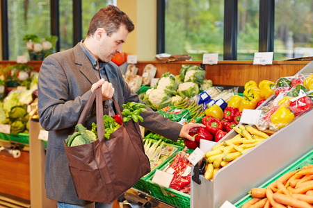 retailer: Businessman with shopping bag buying fresh vegetables in a supermarket Stock Photo