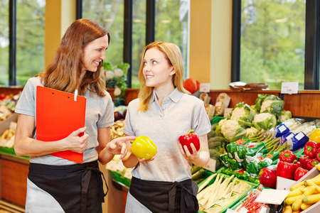 Store manager in supermarket teaching trainee in the vegetables section photo