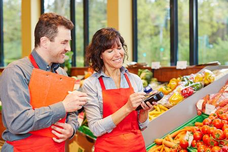 inventory: El personal en el supermercado utilizando terminal de adquisici�n de datos m�viles para la entrega verduras Foto de archivo