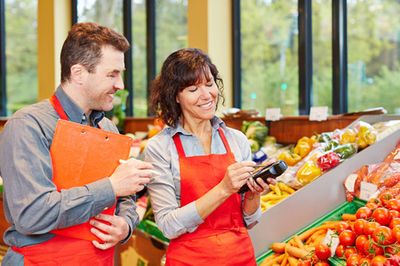 inventory: Staff in supermarket using mobile data acquisition terminal for vegetables delivery