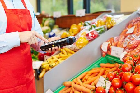 Main de vendeur en utilisant le terminal mobile d'acquisition de données dans un supermarché Banque d'images - 29682803