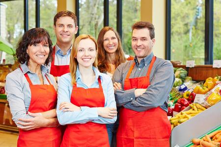 vendedor: Feliz equipo de personal con los hombres y las mujeres en un supermercado