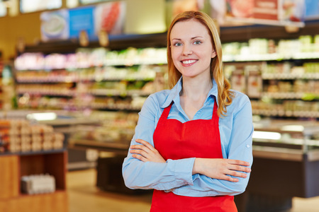 seller: Young happy saleswoman with red apron in a supermarket Stock Photo