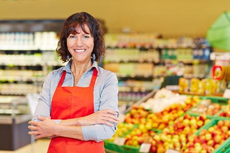 Elderly smiling saleswoman standing with her arms crossed in a supermarket