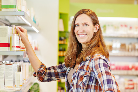Attractive smiling woman buying cosmetis in drugstore department of a supermarket photo