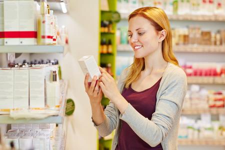 슈퍼마켓의 약국 부서에서 그녀의 손에 화장품을 들고 젊은 여자 스톡 콘텐츠