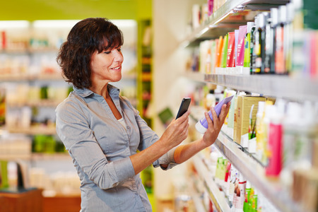 Elderly woman scanning barcode of cosmetics product in a drugstore photo