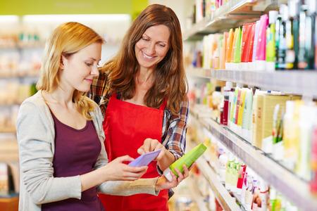 vendedor: Mujer joven comparar productos cosméticos con vendedora en una farmacia Foto de archivo