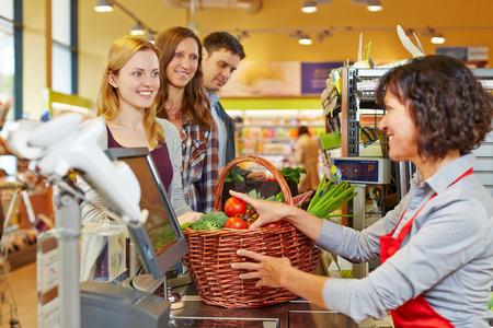 スーパー マーケットのレジで食料品のバスケットを払って若い女性