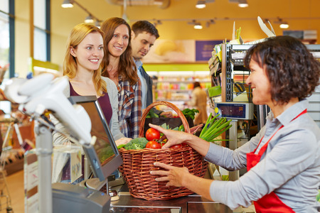 retailer: Young woman paying basket of groceries at supermarket checkout