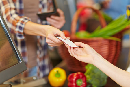 card payment: Hand of customer giving credit card to supermarket cashier at checkout Stock Photo