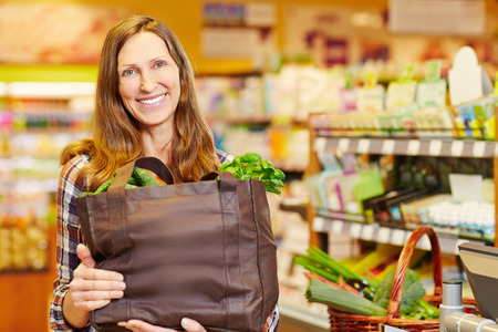 Smiling woman holding full shopping bag with vegetables in organic food store photo