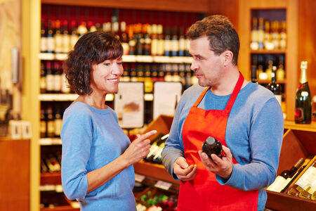 Salesman in supermarket offering bottle of red wine to smiling woman photo