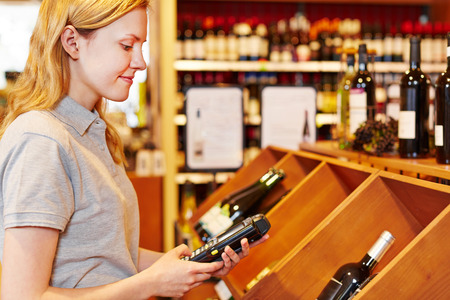 Saleswoman counting wine bottles with mobile data registration terminal photo