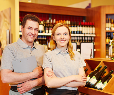 Happy store manager and smiling saleswoman in wine shop photo