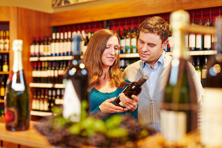 wine trade: Couple buying a bottle of red wine in a supermarket Stock Photo