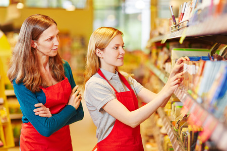 put away: Internship organizing shelves in supermarket under supervision of the store manager