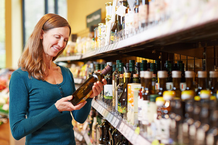 food shelf: Smiling elderly woman buying a bottle of olive oil in a supermarket Stock Photo