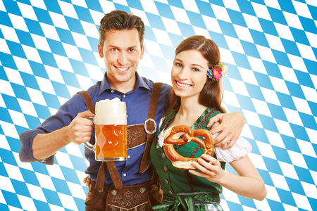 Happy couple at Oktoberfest with beer and pretzel in front of bavarian flag photo