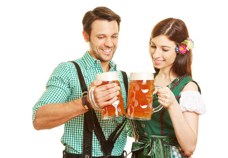 liter: Happy couple in traditional outfit drinking beer in Bavaria at Oktoberfest Stock Photo