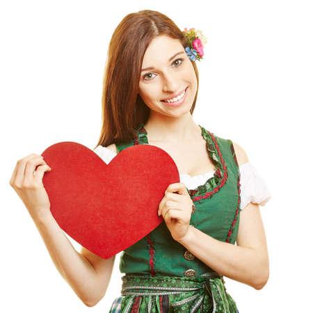 dirndl dress: Smiling woman in dirndl dress holding red heart in Bavaria
