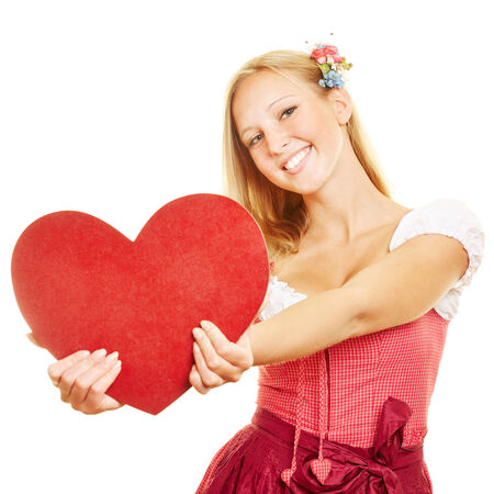 dirndl dress: Happy woman in dirndl dress holding a big red heart Stock Photo