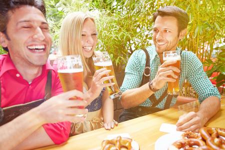 Freunde glücklich lachend in Biergarten in Bayern im Sommer