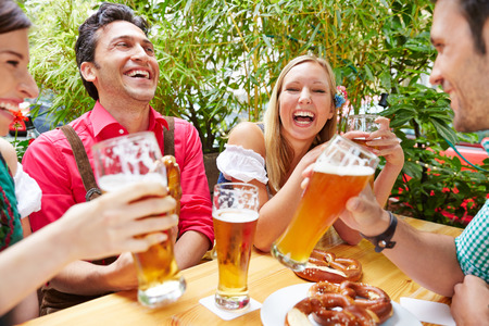 Friends drinking beer and having fun in beer garden in Bavaria Stock Photo