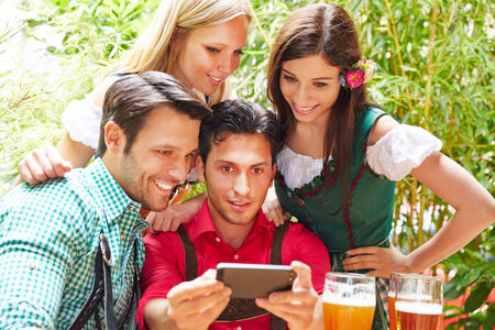 Happy friends taking selfie in bavarian beer garden in summer photo