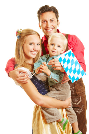 dirndl: Happy smiling family in Germany with son and bavarian flag Stock Photo