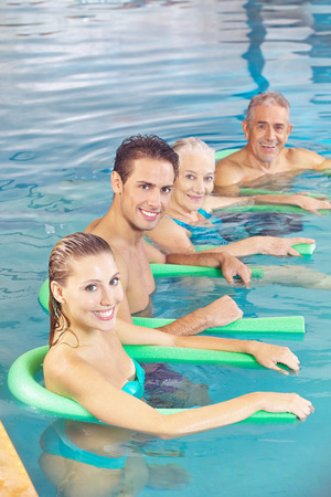 People doing aqua fitness as back training in a swimming pool photo