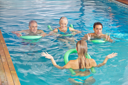 Young woman leading aqua fitness class for senior people in swimming pool photo