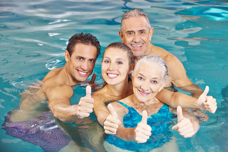 hydrotherapy: Happy family with senior couple in swimming pool holding thumbs up
