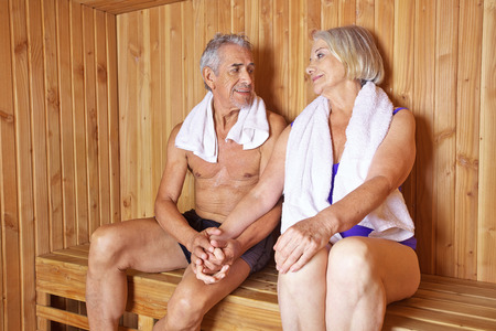 sauna: Two happy seniors holding their hands in a sauna in a hotel Stock Photo