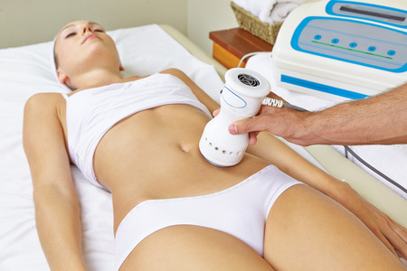 fat burning: Woman receiving electric massage on stomach for muscle training in spa Stock Photo