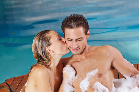 Happy woman kissing man in whirlpool in spa in their holidays photo