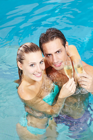 Happy couple drinking glass of sparkling wine in hotel pool photo