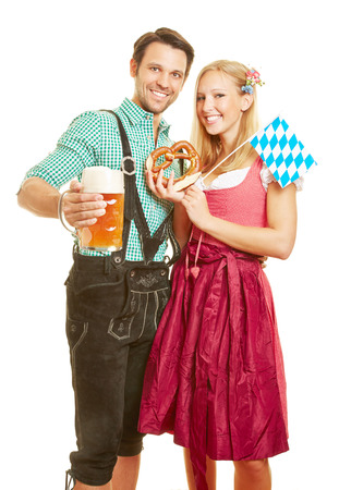 Happy man and smiling woman with beer and pretzel at Oktoberfest in Bavaria Фото со стока