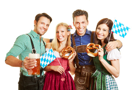 Group of happy friends celebrating Oktoberfest with beer and pretzel in Bavaria Фото со стока